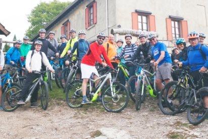 foto di gruppo davanti ad un rifugio con e-bike